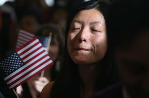 Chinese immigrant and new American citizen Yi Shu holds back tears after taking the oath of citizenship at a naturalization ceremony on April 9, 2013 in New York City. (John Moore/Getty Images)