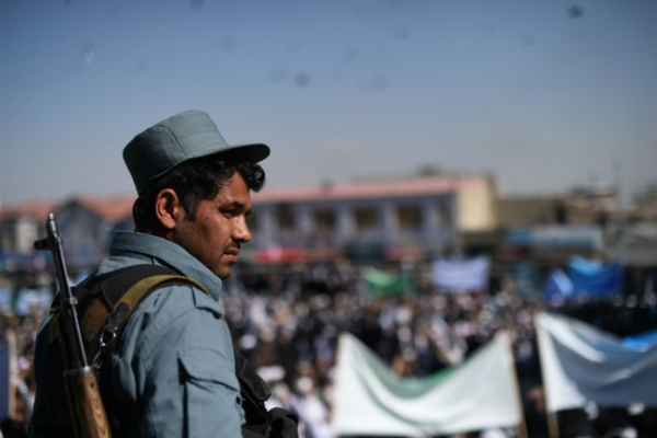 An Afghan policeman keeps watch as clergy men attend a gathering at the Shahi Doshamshira mosque where an Afghan woman, 27, was beaten to death and her body set alight by a mob, in Kabul on March 26, 2015. (Shah Marai/AFP/Getty Images)