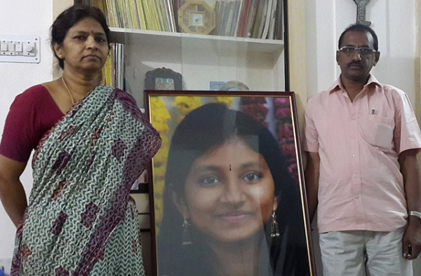 K. Shobha (left) and K. Krishna stand beside a portrait of their daughter, Kasarla Rishitha Reddy, who was among those killed in the Beas River flood. (Tom Lasseter/Bloomberg)