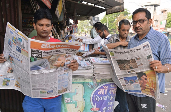 Two men in Amritsar, India read newspapers on April 26, 2015. (Narinder Nanu/AFP/Getty Images)