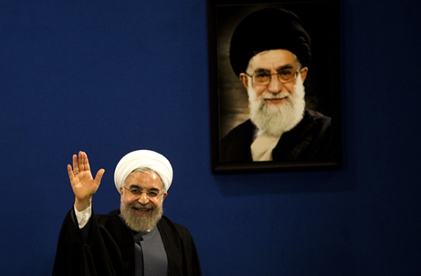 Iranian President Hassan Rouhani waves to journalists next to a portrait of supreme leader Ayatollah Ali Khamenei on June 13, 2015. (Behrouz Mehri/AFP/Getty)