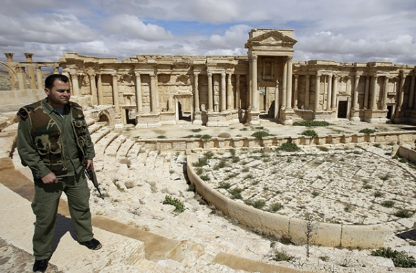 A Syrian policeman patrols Greco-Roman ruins in the ancient city of Palmyra, Syria, on March 14, 2014, before Islamic State forces seized the city the following year. (Joseph Eid/AFP/Getty Images)