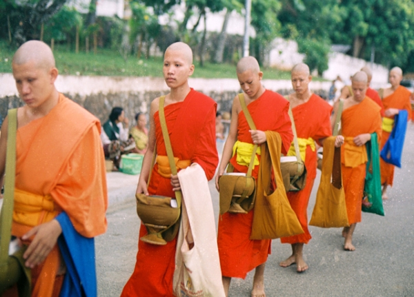 Buddhist men walk down a road in Luang Prabang, one of the Southeast Asian country's most popular tourist destinations. (Khanh Hmoong/Flickr)