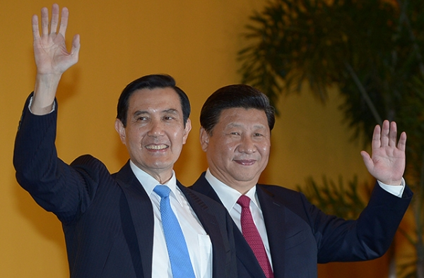 Chinese President Xi Jinping (R) and Taiwan President Ma Ying-jeou wave to journalists prior to a meeting at Shangrila hotel in Singapore on November 7, 2015. It was the first time in nearly seven decades that the top leaders of China and Taiwan met. (Mohd Rasfan/AFP/Getty Images)