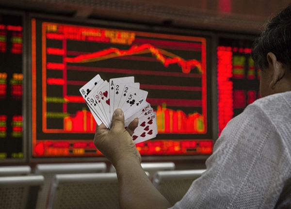 A Chinese day trader plays cards with others as he watches a stock ticker at a local brokerage house on August 27, 2015 in Beijing, China. (Kevin Frayer/Getty Images)