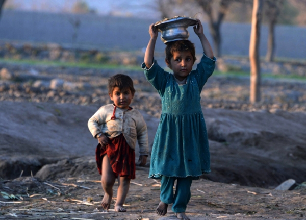 Young Afghan children carry cow dung, to be used as fuel, as they walk on the outskirts of Jalalabad. (Noorullah Shirzada/AFP/Getty Images)