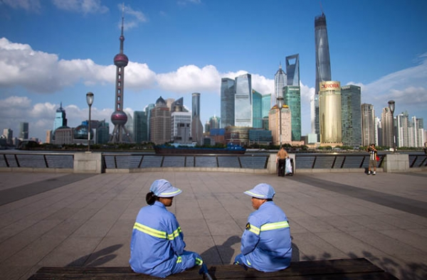 Two cleaners have a rest on a bench at the Bund before the Huangpu River and the skyline of the Lujiazui Financial District in Shanghai. (Johannes Eisele/AFP/Getty)
