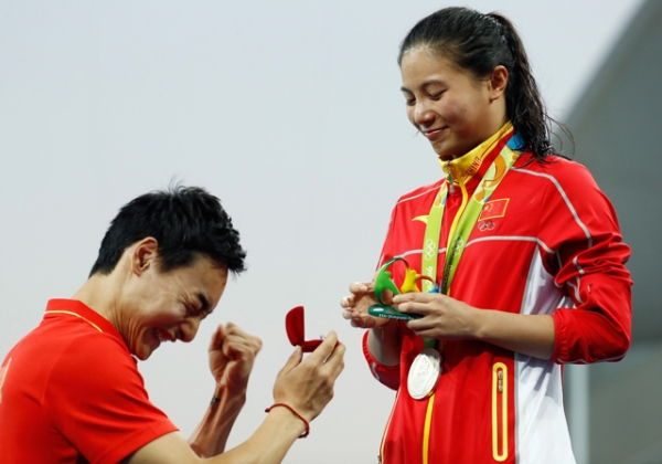 Chinese diver Qin Kai proposes to silver medalist He Zi of China on the podium during the medal ceremony for the Women's Diving 3m Springboard Final. (Clive Rose/Getty Images)