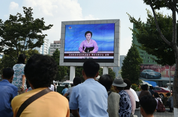 Residents look up at a big screen TV in front of Pyongyang railway station showing television presenter Ri Chun-Hee officially announcing that the country successfully tested a nuclear warhead earlier in the day on September 9, 2016. (Kim Won-Jin/AFP/Getty)