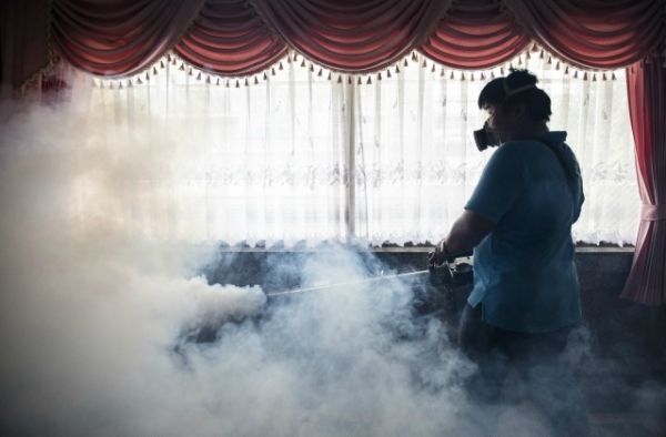 A city worker sprays chemicals with a fumigator to kill mosquitoes in an effort to control the spread of the Zika virus at a school in Bangkok on September 14, 2016. (Lillian Suwanrumpha/AFP/Getty Images)