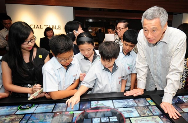 Singapore Prime Minister Lee Hsien Loong (R) and school children look at digital interactive media during the opening of the newly restored National Gallery in Singapore on November 23, 2015. (Mohd Fyrol/AFP/Getty)