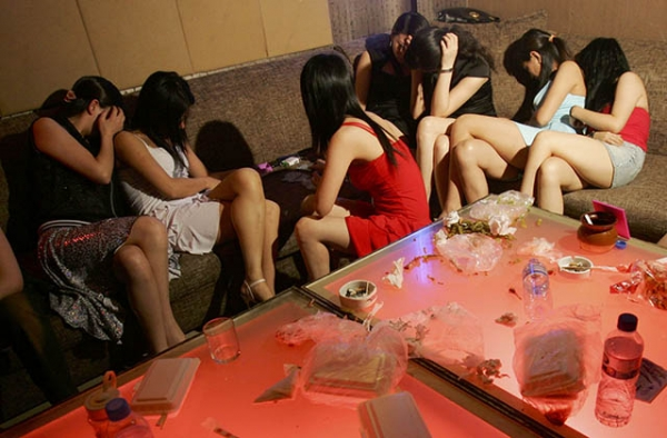 Women hide their faces as police raid an entertainment venue in Beijing, China suspected of offering prostitution services. (China Photos/Getty)