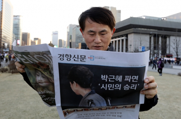 South Korean man reads extra edition newspaper reporting impeached President Park Geun-hye on March 10, 2017 in Seoul, South Korea. (Chung Sung-Jun/Getty Images)
