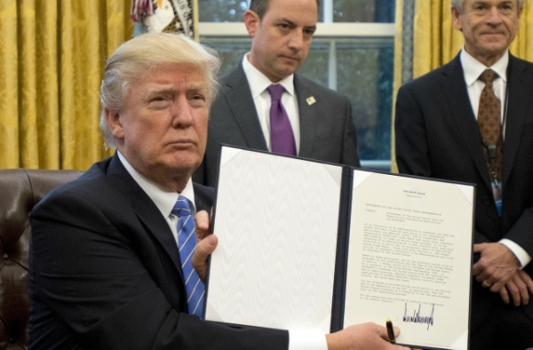 U.S. President Donald Trump shows the Executive Order withdrawing the US from the Trans-Pacific Partnership (TPP) after signing it in the Oval Office of the White House in Washington, DC on Monday, January 23, 2017. (Ron Sachs/Pool-Getty Images)