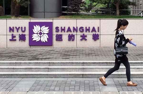 A student walks past the entrance to New York University's Shanghai campus. (Eric Fish/Asia Society)