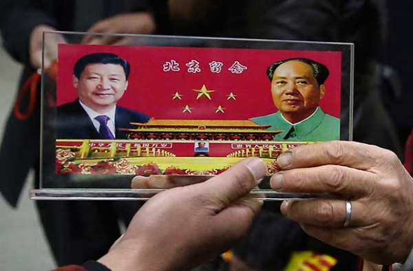 A vendor displays a souvenir with pictures of Chinese President Xi Jinping (Left) and the late Chinese Chairman Mao Zedong (Right) to visitors at the underpass outside the Great Hall of the People. (Feng Li/Getty)