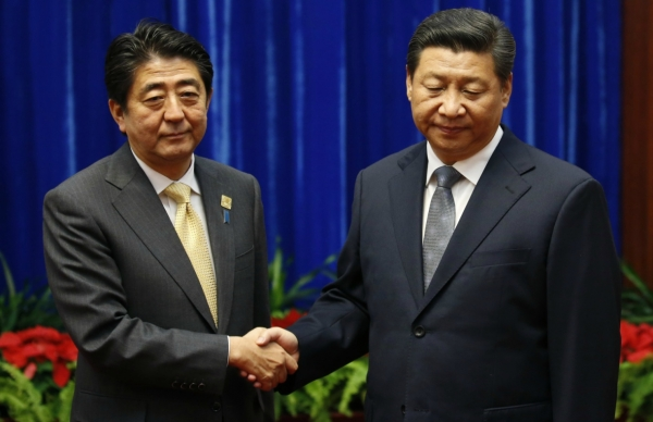 Japan's Prime Minister Shinzo Abe shakes hands with China's President Xi Jinping (R), during their meeting at the Great Hall of the People, on the sidelines of the Asia Pacific Economic Cooperation (APEC) meetings, November 10, 2014 in Beijing, China. (Kim Kyung Hoon/Pool-Getty Images)
