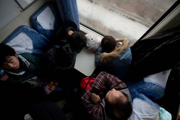 On January 31, 2013, Lunar New Year travellers sleep aboard a train bound for the southwestern Chinese city of Chongqing from Beijing, a journey of 32 hours. (Ed Jones/AFP/Getty Images)