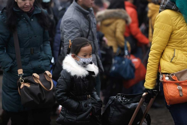 A Chinese girl with a face mask prepares to travel at the Beijing Railway Station in Beijing, China on January 31, 2013. (Lintao Zhang/Getty Images)