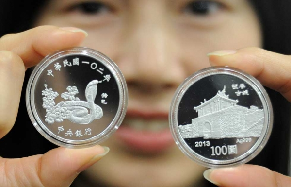 A woman displays two silver coins with designs of a snake (L) and the ancient southern town Hangtsun during a press conference at the Central Bank in Taipei, Taiwan on January 8, 2013. (Sam Yeh/AFP/Getty Images)