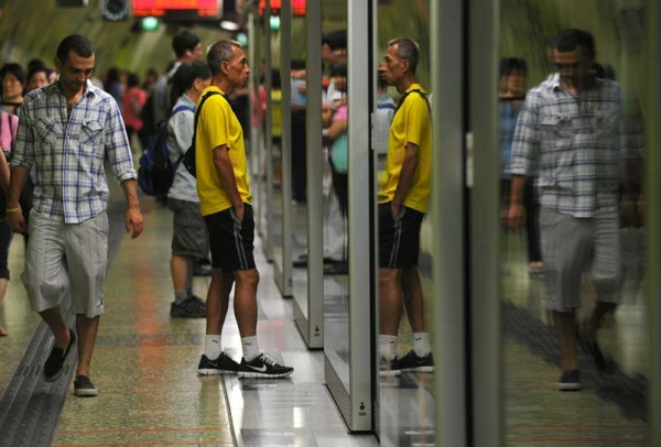 Underground train passengers are reflected in glass doors as they await a train in Hong Kong on June 22, 2012. Hong Kong's system features free WiFi in 42 stations. (Antony Dickson/AFP/GettyImages)