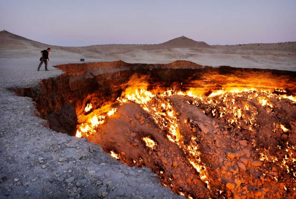 The Darvaza gas crater in the desert of Turkmenistan. In the 1970s the Soviets were drilling for gas and collapsed this crater. The huge outpouring of gas posed a danger for nearby villages so the crater was lit, and has been burning ever since. (Amos Chapple)