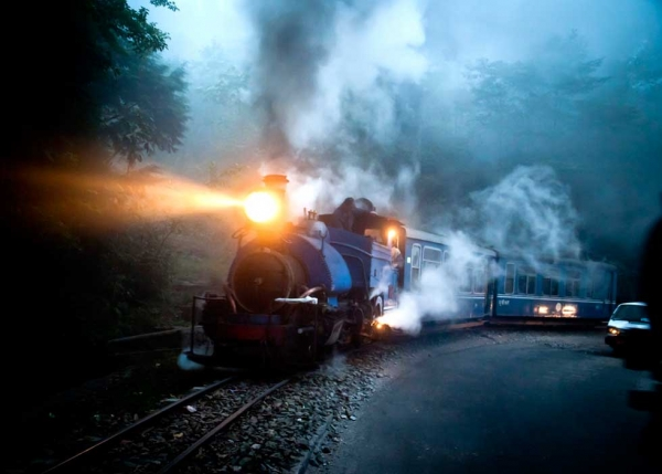 In India, the Darjeeling mountain train puffs through mist on a winter's evening. (Amos Chapple)