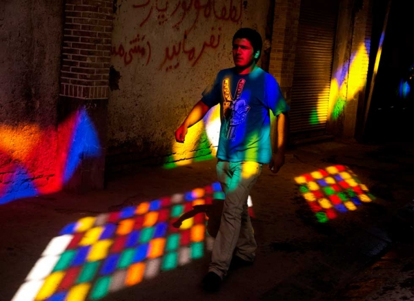 A young Iranian man walks through light from a stained glass window in Tehran Bazaar. (Amos Chapple)