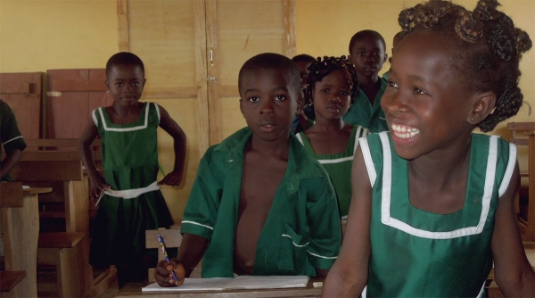 Students smile in a classroom in Africa.