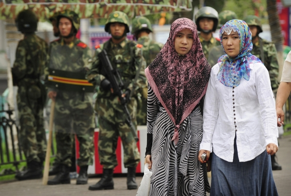Two ethnic Uighur women pass Chinese paramilitary policemen standing guard outside the Grand Bazaar in the Uighur district of the city of Urumqi