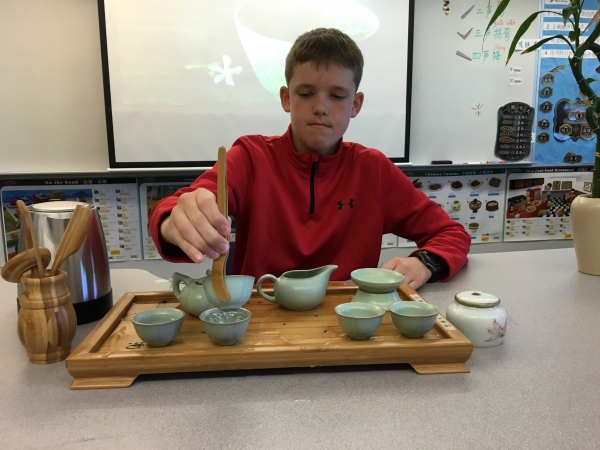 A middle school student demonstrates a tea ceremony to his class.