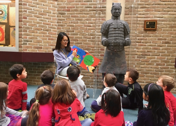 A teacher reads to her immersion students next to a life-size replica of a Terracotta warrior.