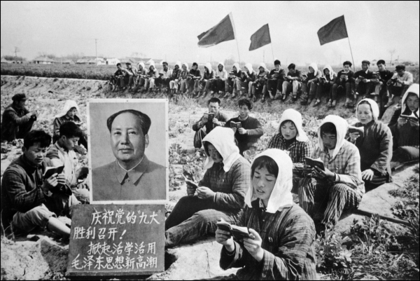 Agricultural workers in China read the Little Red Book beside a portrait of Chairman Mao Zedong during the Cultural Revolution