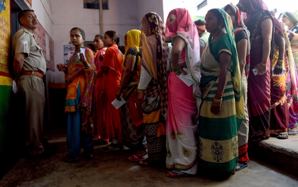 Indian voters queue to cast their vote at a polling station during India's general election in Aligarh.