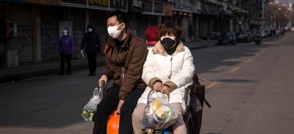 Two residents wear a protective mask as they ride by a bicycle in the street on February 5, 2020, in Wuhan, Hubei province, China. Flights, trains and public transport including buses, subway, and ferry services have been closed for the 14th day. (Getty Images)