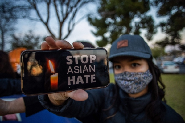 Julie Tran holds her phone during a candlelight vigil in Garden Grove, California, on March 17, 2021 to unite against the recent spate of violence targeting Asians and to express grief and outrage after yesterday's shooting that left eight people dead in Atlanta, Georgia, including at least six Asian women.