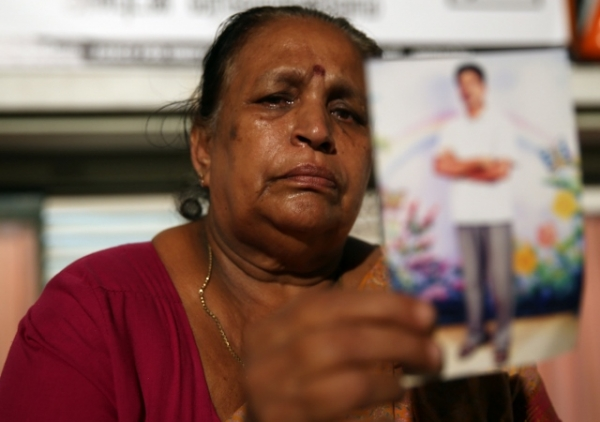 A woman belonging to the Sri Lankan minority Tamil ethnic group holds a photo of her son, who disappeared during the final stage of the Sri Lankan civil war, at a human rights protest festival on November 13, 2013 in Colombo, Sri Lanka. (Buddhika Weerasinghe/Getty Images)