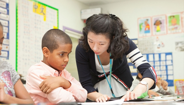 5th grade student going over a lesson with his teacher. (Ann-Marie VanTassell Photography)