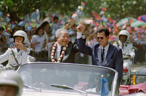 Sihanouk (C) and Cambodian Prime Minister Hun Sen (R), leader of the formerly communist Cambodian People's Party, clasp hands in a motorcade from the Phnom Penh airport following the Prince's arrival in November 1991, after 13 years in exile. (Dominique Faget/AFP/Getty Images)