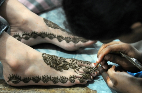 A Karachi beautician applies traditional henna designs to the foot of a customer at a beauty salon ahead of Eid-ul-Fitr in 2009. (Asif Hassan/AFP/Getty Images)