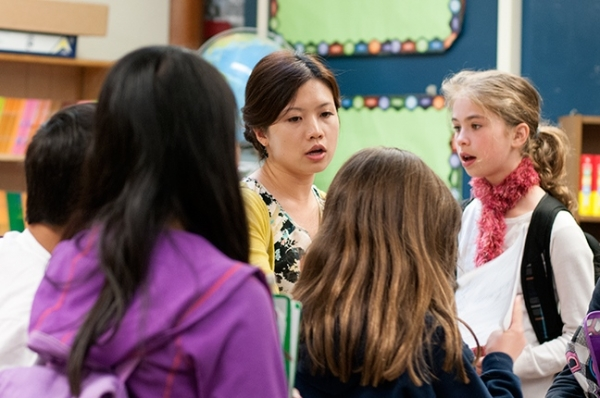 5th grade Mandarin Immersion students gather around their teacher in conversation at Beacon Hill International School.