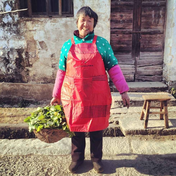 Auntie Wang, a Bishan local farmer, with a basket of daikon leaf. She picked the leaves to give to Ou Ning's mother. (Sun Yunfan)