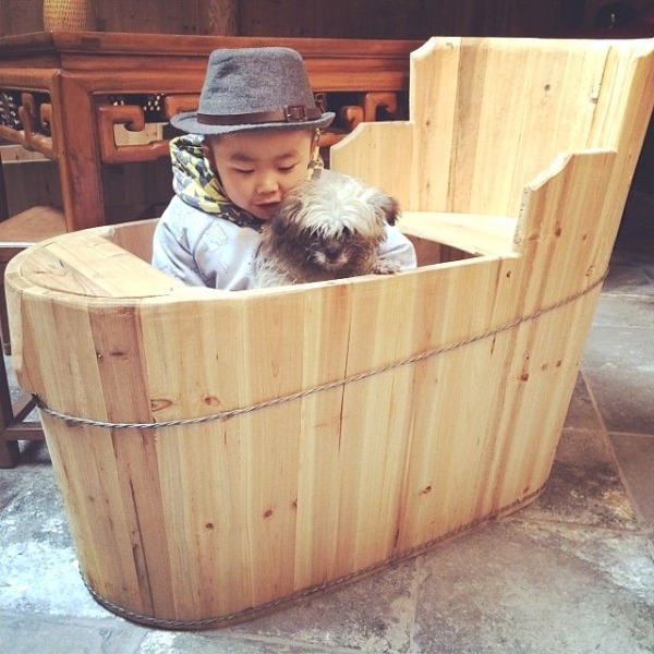 Tangtang, Ou Ning's fiance's son, sitting with his pet dog Gutou in a huotong, a local heating device made of a wooden barrel holding charcoal at the bottom. (Sun Yunfan)