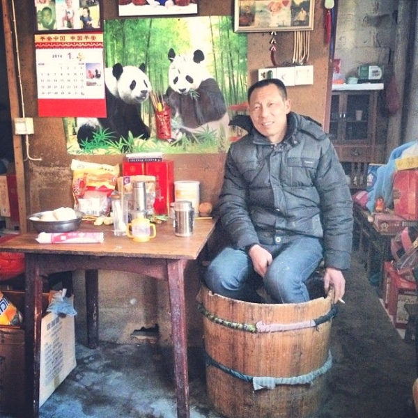 A shop owner in Bishan sits in his huotong while watching over his shop. (Sun Yunfan)