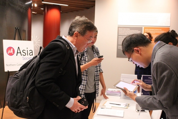 Alex Kwok (right) of ASNC assists a guest at check-in. (Yiwen Zhang/Asia Society)