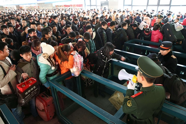 Passengers prepare to board the trains that will eventually take them home for the Spring Festival on January 26, 2014 in Beijing, China. (ChinaFotoPress/Getty Images)