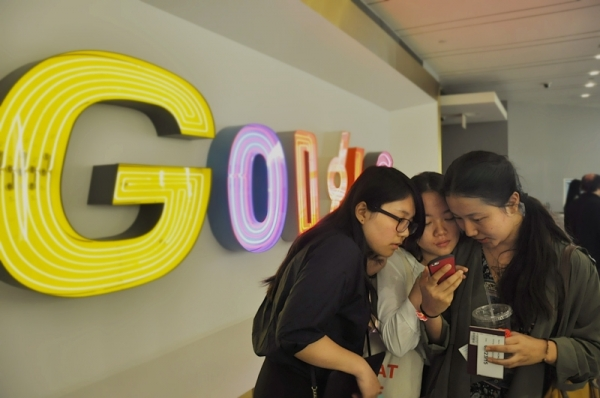 (Left to right) Young Scholars Hong Xinyu, Dang Weikun and Pingcuo Zhuoma review pictures from meetings at the New York City offices of Google Inc. A tour and meetings with Google employees gave the Young Scholars the opportunity to learn about how civic mindedness shapes Google's products, corporate mission, and mindset. (Zhangbolong Liu & Zhu Xi/Google NYC Offices)