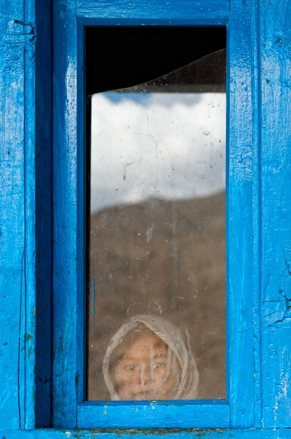 A girl peers out a brilliant blue window in Khangral. (Anjum Vahanvati)