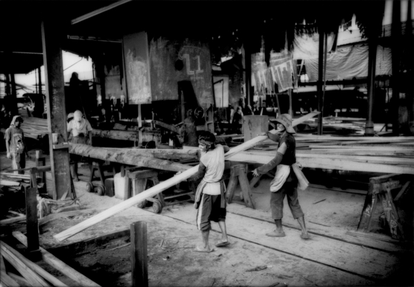 Workers cut logs from the Borneo rainforest into planks of lumber for export in one of the sawmills that line the banks of Batan. (James Whitlow Delano)