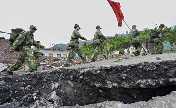 Chinese soldiers walk along a collapsed section of a mountain road in Wenchuan County as they make their way to the earthquake epicenter of Wenchuan City on May 14, 2008. (Teh Eng Koon/AFP/Getty Images)